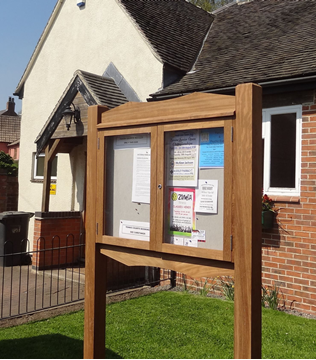 Double Door Noticeboard outside a community centre showing local notices. Post-mounted on two legs.
