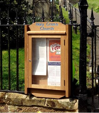 Noticeboard with engraved header sign at the top, located outside a church with church notices inside it, behind the locked glass panel